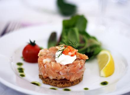 En av våra förrätter: Rökt lax & skaldjurstartar på kavring serveras med örtsallad & pepparrotscrème